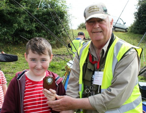 This Young Angler Receives His Trophy from Tom Cogan