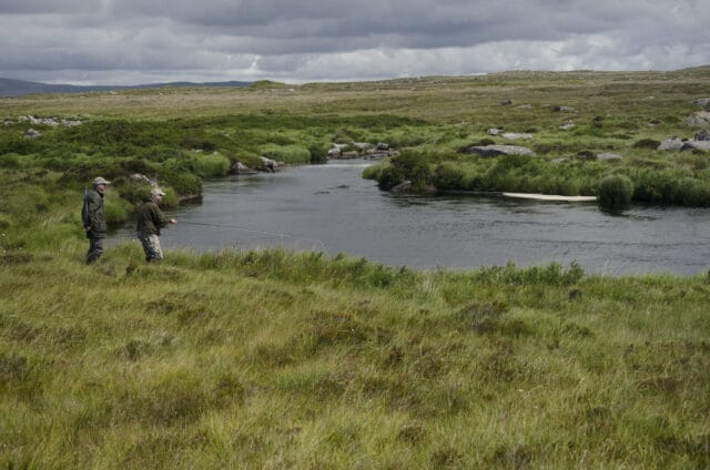 Anglers on river set in wild bogland scenery with mountains in far distance