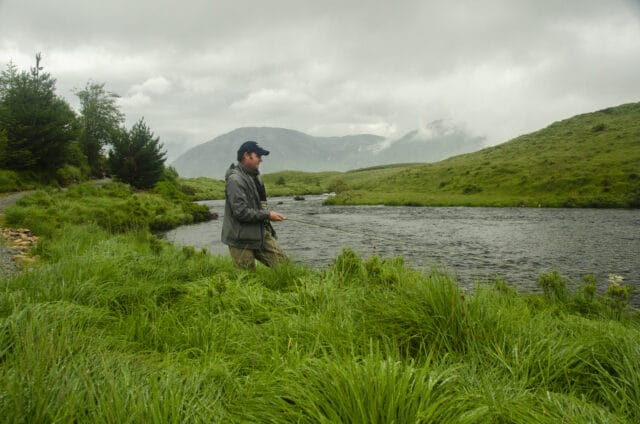 Angler fishing on river with mountains in background
