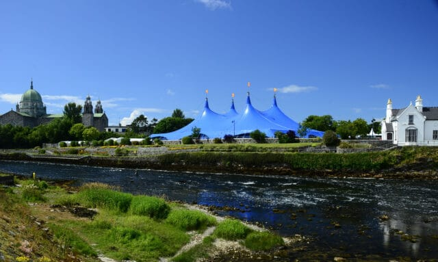 River with cathedral and concert tent in background