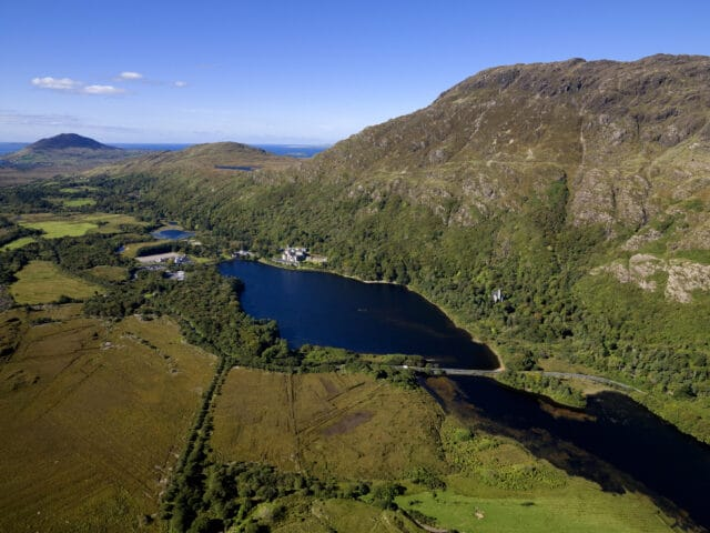 Aerial view of Kylemore Abbey and lakes with mountain in background