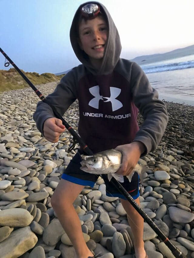Young angler on beach holding a bass