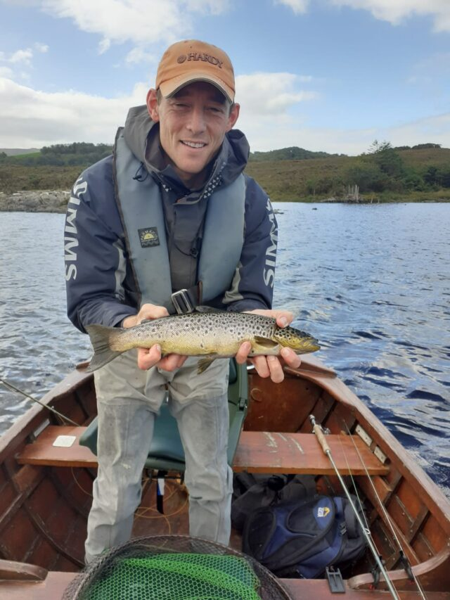 Angler i boat holding trout