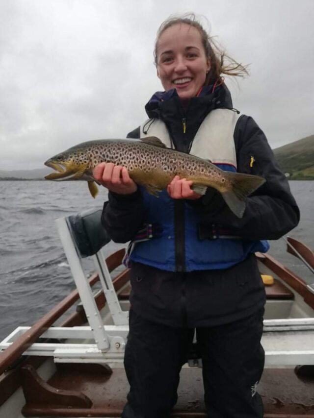 Lady angler in boat holding fine trout