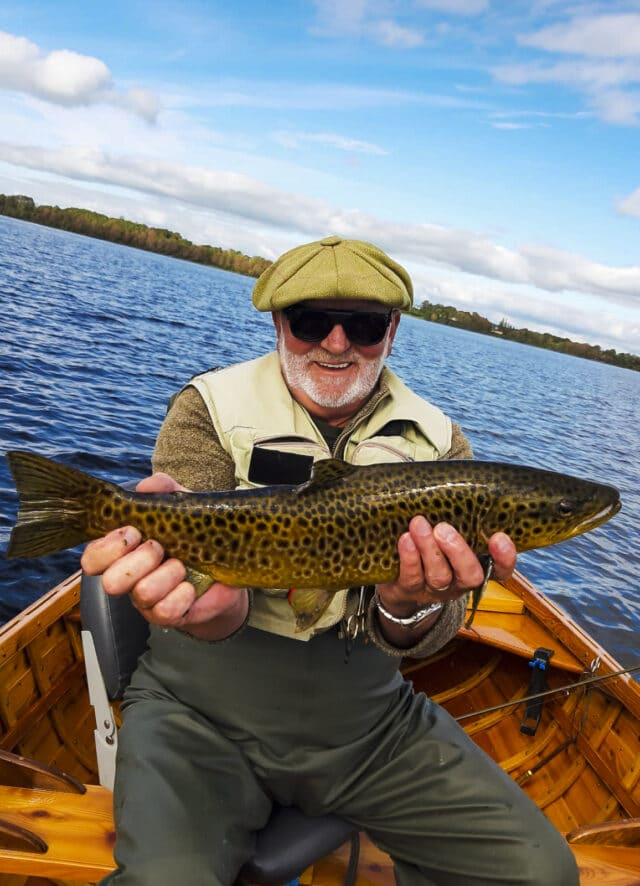 Angler in boat holding trout